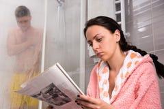 Молодая женщина в купальном халате читая газету и ждать ее Стоковое Изображение