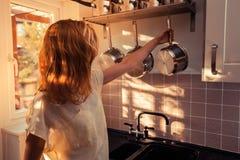 Молодая женщина в кухне варя с кастрюлькой стоковые фото