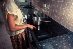 Молодая женщина в кухне варя с кастрюлькой стоковые изображения rf