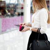 Молодая женщина в модных одеждах смотря в бумажник в sho Стоковая Фотография
