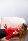 Молодая женщина в музыке наушников слушая ослабляя дома дальше так Стоковое Фото