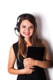 Молодая женщина в наушниках и микрофоне при изолированная таблетка, Стоковые Фото