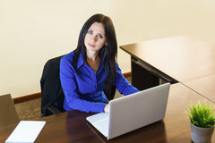Молодая женщина в офисе работая на белой компьтер-книжке Стоковая Фотография