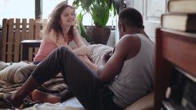 Молодая женщина в пижамах представляя к фотографу Красивый человек принимает фото на старой камере двигать-фильма в кровати Стоковые Изображения
