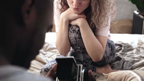 Молодая женщина в пижамах представляя к фотографу Человек принимает фото на старой камере двигать-фильма, смотрит видеозаписывающ Стоковая Фотография