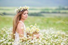 Молодая женщина в поле зацветая маргариток Стоковые Фото
