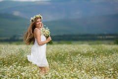 Молодая женщина в поле зацветая маргариток Стоковое Фото