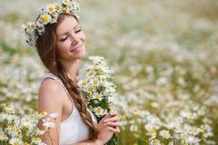 Молодая женщина в поле зацветая маргариток Стоковая Фотография