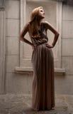 Молодая женщина в платье лета против старой каменной стены Стоковые Фото