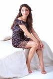 Молодая женщина в платье сидит на крае кровати Стоковое фото RF