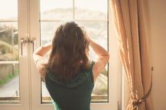 Молодая женщина в платье смотря вне окно стоковая фотография rf