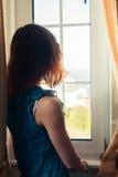 Молодая женщина в платье смотря вне окно стоковые изображения