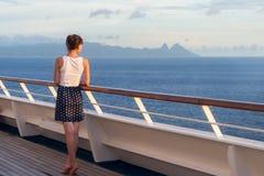 Молодая женщина в платье стоит на палубе вкладыша и взгляда круиза Стоковое Изображение RF