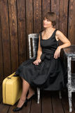 Молодая женщина в ретро платье черноты стиля с винтажным чемоданом Стоковое Изображение RF