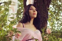 Молодая женщина в розовом платье на качании Стоковая Фотография