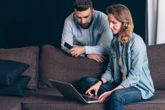 Молодая женщина в рубашке джинсовой ткани, сидя дома на кресле и используя компьтер-книжку Гай держа smartphone Стоковое Изображение
