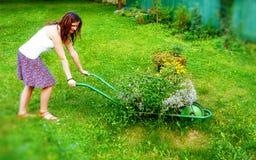 Молодая женщина в саде шаловливо нажимая декоративную тачку вполне цветков Стоковая Фотография