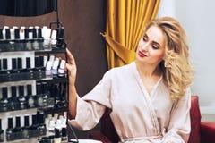Молодая женщина в салоне ногтя выбирая цвет маникюра для того чтобы примениться Стоковые Фотографии RF