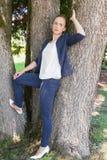 Молодая женщина в склонности синего пиджака против деревьев стоковые изображения