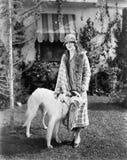 Молодая женщина в снаружи пальто и шляпы стоящем с ее русским Wolfhound (все показанные люди нет более длинные живущих и никакого Стоковые Фото