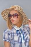 Молодая женщина в солнечных очках и соломенной шляпе стоковое изображение