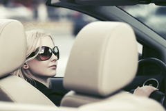 Молодая женщина в солнечных очках управляя обратимым автомобилем стоковые изображения