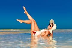 Молодая женщина в соломенной шляпе кладя на тропические пляж и enjoyi стоковая фотография