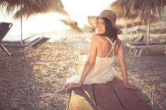 Молодая женщина в соломенной шляпе сидя на тропическом пляже, наслаждающся песком и заходом солнца Класть в тень парасолей пальмы Стоковые Фото