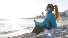 Молодая женщина в спорте одевает питьевую воду после разминки на пляже сток-видео