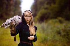 молодая женщина в средневековом платье с сычом на ее руке стоковое фото
