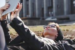 Молодая женщина в стеклах используя лежать таблетки внешний в городе стоковое фото