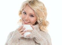 Молодая женщина в теплом свитере и кружке в его руках стоковая фотография