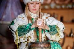 Молодая женщина в традиционном платье производящ масло от молока дома стоковые изображения