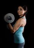 Молодая женщина в тренировке с гантелями на черном bakground, sporty мышечное женское брюнет фитнеса Стоковые Изображения RF