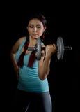 Молодая женщина в тренировке с гантелями на черном bakground, sporty мышечное женское брюнет фитнеса Стоковое Изображение