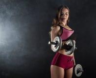 Молодая женщина в тренировке с гантелями, sporty мышечное женское брюнет фитнеса в дыме Стоковые Изображения