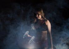 Молодая женщина в тренировке с гантелями, sporty мышечное женское брюнет фитнеса в дыме Стоковая Фотография RF