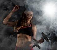 Молодая женщина в тренировке с гантелями, sporty мышечное женское брюнет фитнеса в дыме Стоковое Изображение