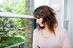 Молодая женщина в ультрамодном офисе смотря вне окно Стоковые Изображения RF