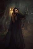 Молодая женщина в черной робе при длинные волосы смотря сразу на c Стоковое Изображение RF