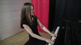 Молодая женщина в черном платье играя на рояле видеоматериал