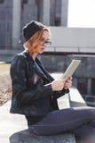 Молодая женщина в черноте использует таблетку внешнюю в городе стоковая фотография