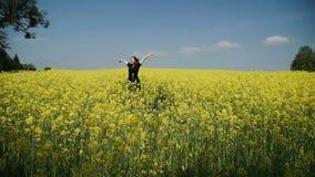 Молодая женщина в черноте одевает прозодежды бежать через hd цветков желтого поля касающее акции видеоматериалы
