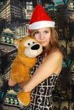Молодая женщина в шлеме Санты с игрушкой Стоковая Фотография