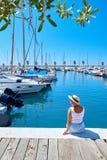 Молодая женщина в шляпе и милое лето одевают на пристани Гавань парусника стоковое фото