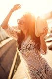 Молодая женщина в шляпе и милое лето одевают положение на пристани при мирный пейзаж городка, смотря заход солнца стоковое изображение
