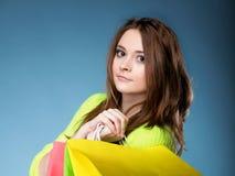 Молодая женщина с бумажной multi покрашенной хозяйственной сумкой Стоковое фото RF