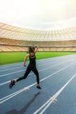 Молодая женщина в sportswear sprinting на идущем стадионе следа на заходе солнца Стоковые Изображения