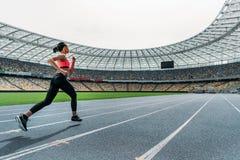 Молодая женщина в sportswear sprinting на идущем стадионе следа Стоковые Изображения