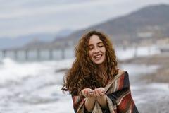 Молодая женщина в striped плащпалате держа камешки в ее ладонях Стоковое фото RF
